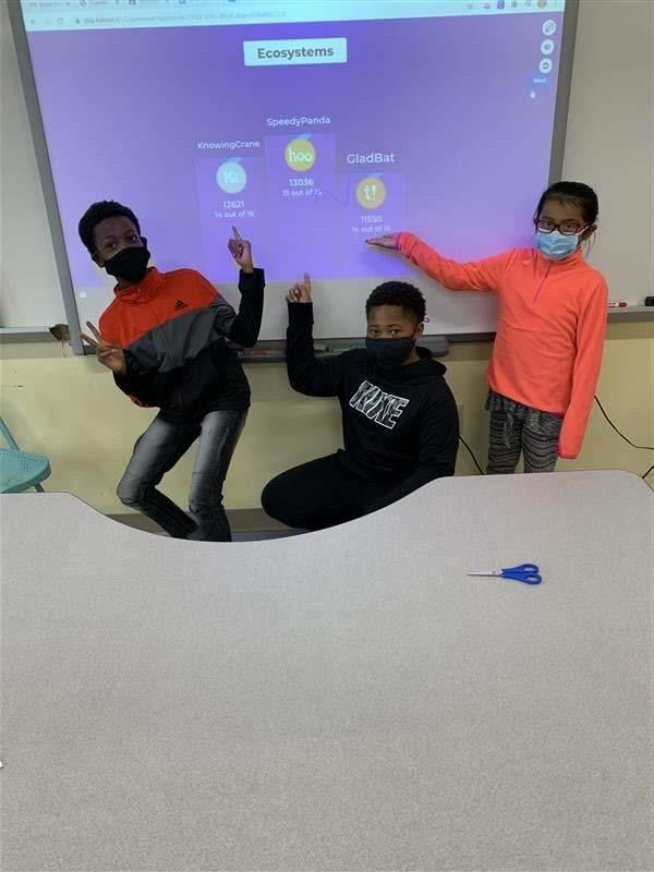 3 boys showing ecosystems on the smartboard