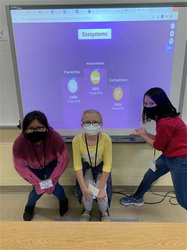 3 girls showing ecosystems on smartboard