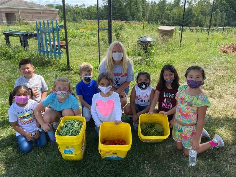 Mrs. Retiz's class pose with the freshly picked vegetables from the Stewart garden.